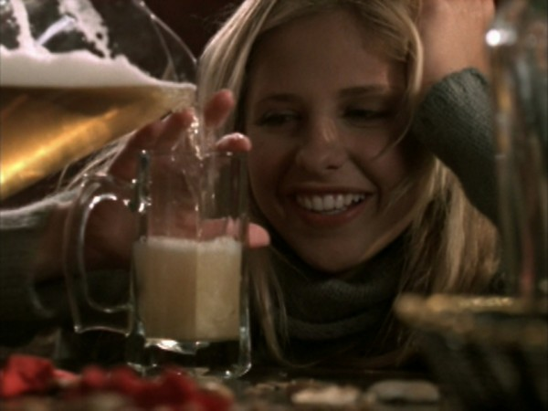 Buffy smiles tipsily as someone pours a beer.