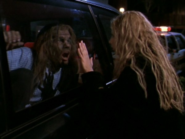 Buffy looks at a caveman through a car window