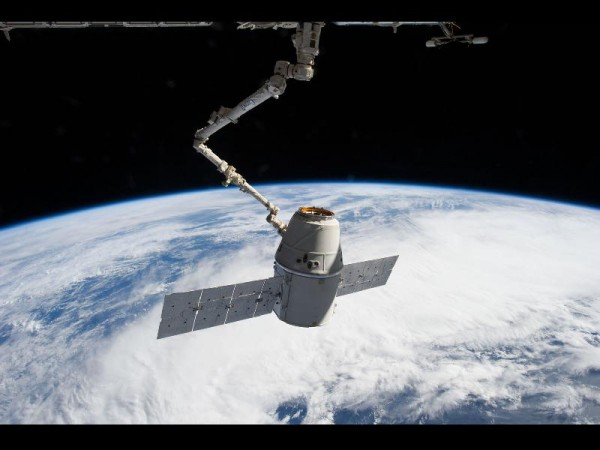 Robotic arm of the International Space Station reaching out to the Dragon capsule for docking. The edge of the earth is in the background.