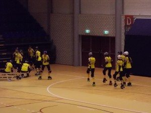Several women in matching yellow and black uniforms dance on roller skates