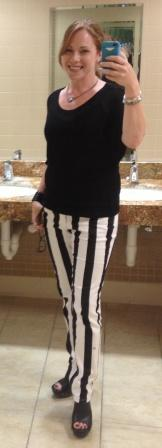 Selfie of Kym in black and white stripe pants and a black shirt in the bathroom at her office