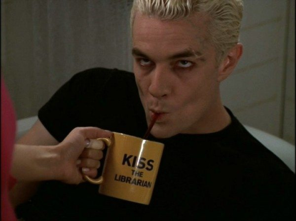 "Spike drinking from a ""Kiss the Librarian"" mug."