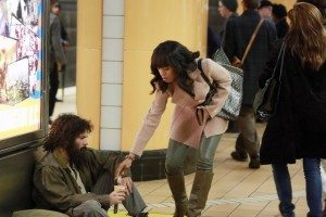 Olivia gives money to Huck, who is panhandling in the train station