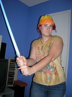 Tashi wearing Jayne hat and wielding a light saber