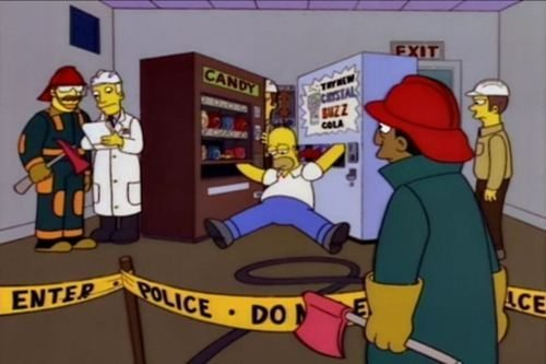 Homer Simpson with one hand stuck in a candy machine and the other stuck in a soda machine, surrounded by first responders and police tape