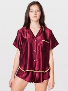 Model wearing burgundy satin pajama top and shorts