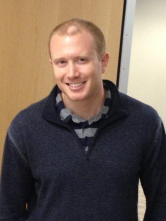photo of young redheaded man wearing a blue and grey striped shirt and a blue sweater smiling