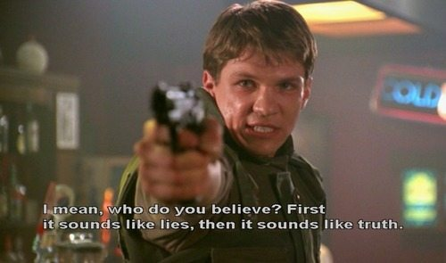"""Riley aims a gun, captioned """"I mean, who do you believe? First it sounds like lies, then it sounds like truth."""""""