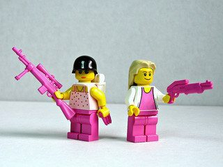 Lego figures dressed in pink hold large plastic weapons.