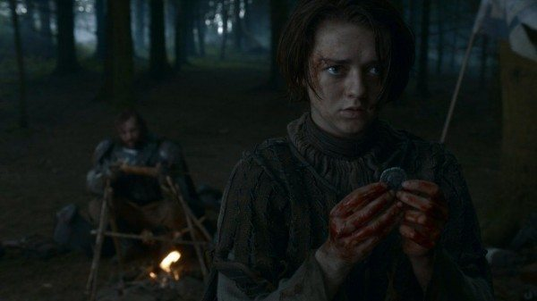 Arya holds her iron coin with bloody hands, while The Hound eats the Freys' food behind her