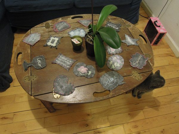 Finished coasters, with names written on them, scattered on a table. A cat peeks out form under the table.