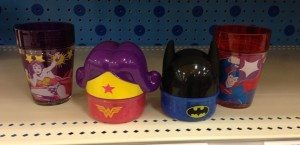 Pink, purple, and yellow Wonder Woman cup and snack container next to a blue and black Batman snack container and red and blue Superman cup.