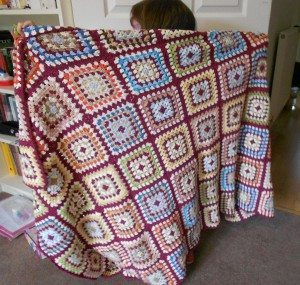 Child holding up finished blanket
