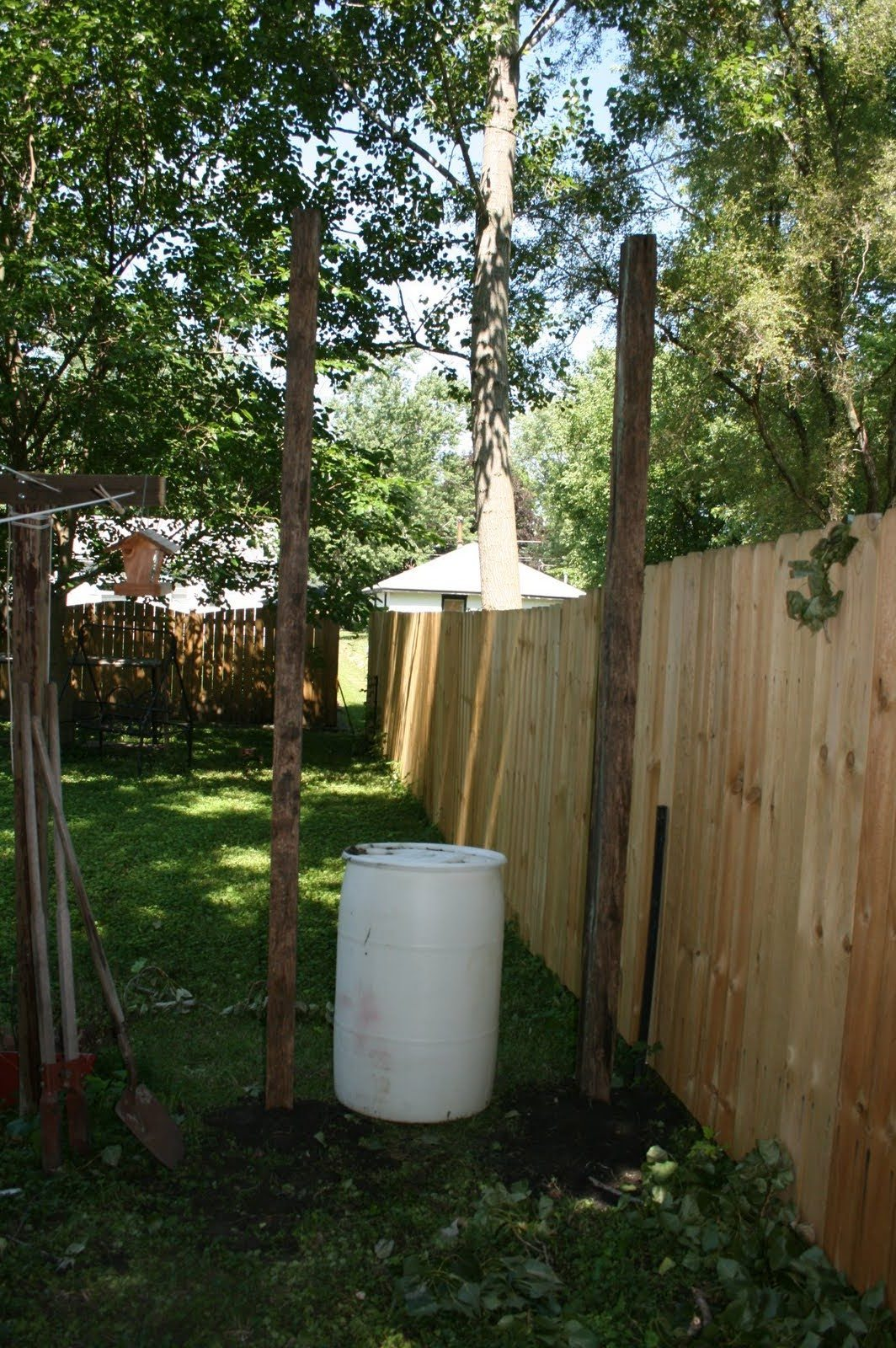 Barrel and two posts in yard next to fence