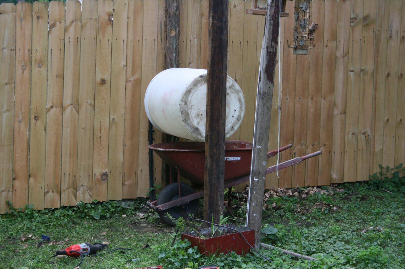 One barrel suspended between poles with a wheelbarrow underneath
