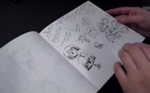 Hands flipping through a sketchbook