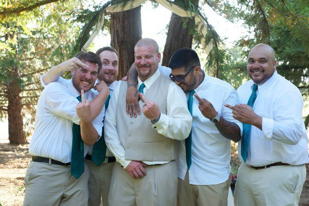 Photo of 5 men flipping off the camera. all are in white shirts, teal ties and khaki pants