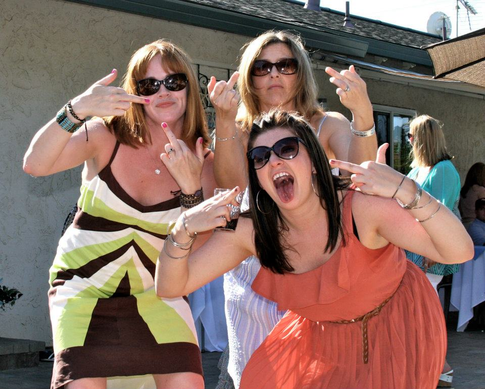 photo of three women in dresses, one green brown and white, one purple, one orange, flipping off the camera with both hands and making funny faces
