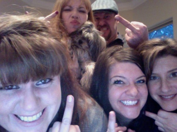 up close web cam photo of 4 women, 1 guy and a dog flipping off the camera and making funny faces