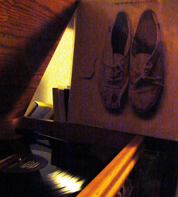 A picture of a record player with a record and an album cover featuring a pair of old shoes.