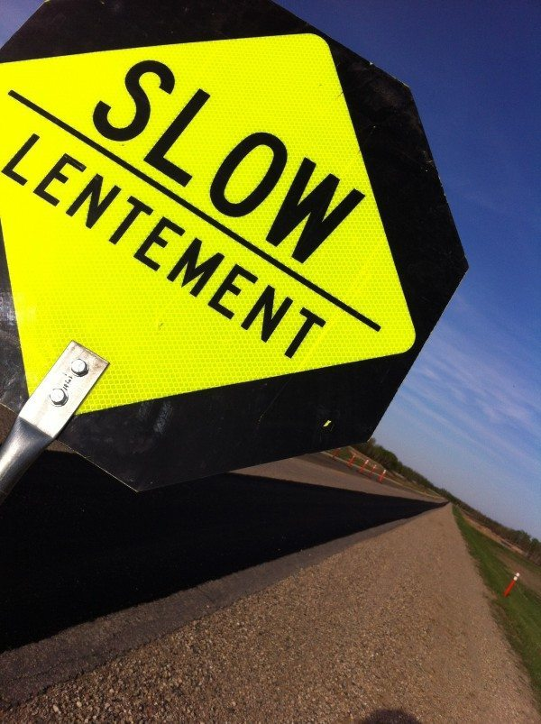 "Closeup of a road sign that says ""Slow"" in English and French"