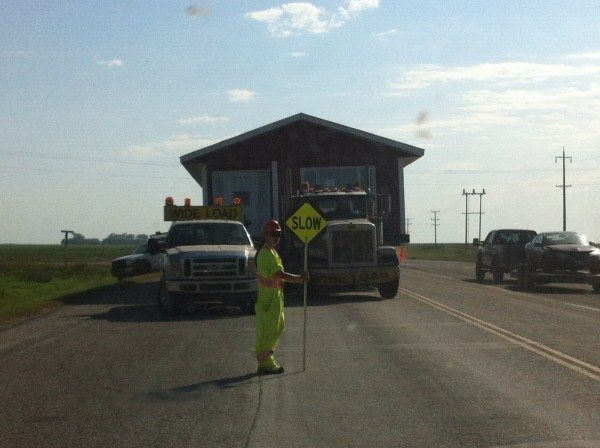A flagger in reflective gear stands in front of a line of cars and trucks, including a house on a flatbed