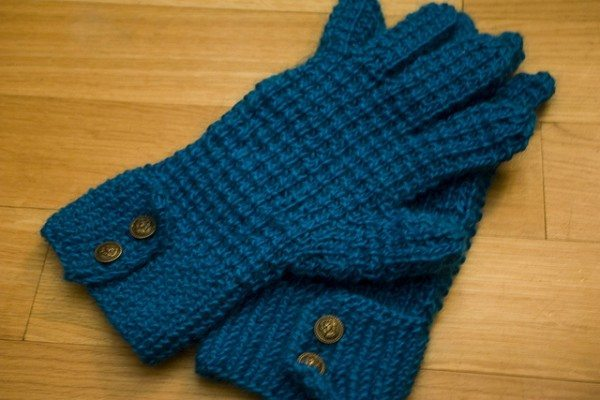 A pair of blue knit gloves laying on a hardwood floor.