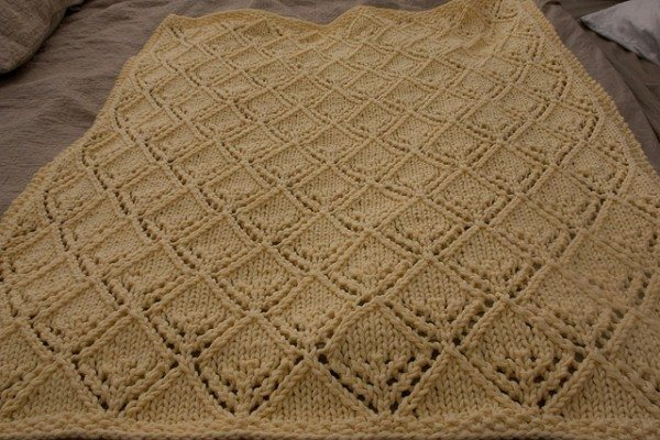 A hand knit butter yellow baby blanket.