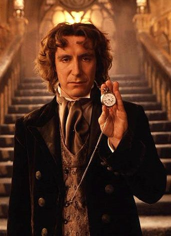 The eighth Doctor from Doctor Who holds a time piece.