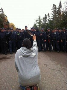 Man kneels before Royal Candian Mounted Police with eagle feather