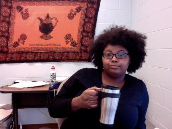A picture of a Black woman with curly hair and glasses, drinking from a silver travel mug while sitting in front of an orange cloth with a teapot print.