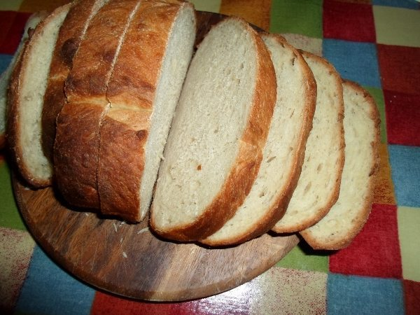 A sliced loaf of break on a wooden cutting board.