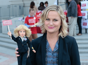 "Image of Leslie Knope (Amy Poehler) and a doll calling for her recall in NBC's ""Parks and Recreation"" episode 6.05 ""Gin it Up!"""