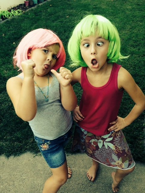 photo of two young girls making silly faces wearing a hot pink and neon green wig. One is in a dark pink tank top and multi-colored skirt and the otehr wears a grey tank and denim shorts