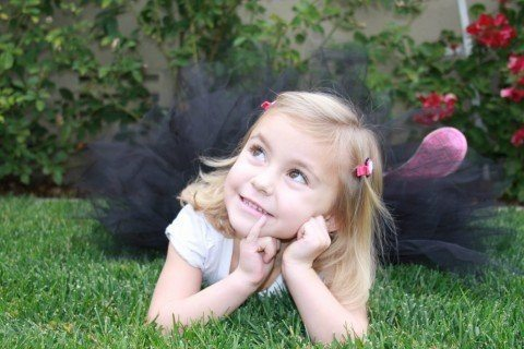 young blond girl in a black tutu and white tee with pink barrettes laying in the grass with her chin in her hands