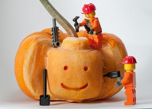 Tiny lego men carving a friendly face into a pumpkin.