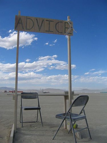 """Cardboard sign above two folding chairs reads """"advice"""""""