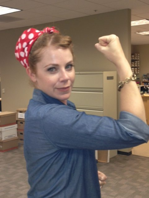 photo of Kym dressed as Rosie the Riveter in a denim shirt with the sleeves rolled up and a red bandanna tied around her hair holding one arm up and flexing her muscles