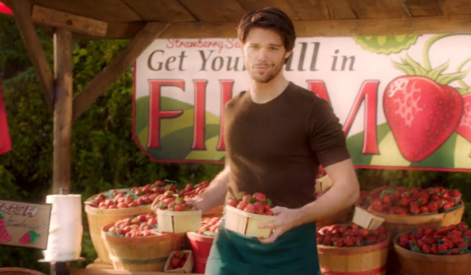 Photo of a TV screen grab of Kym's brother, Steven, a brown haired man in a dark tee and jeans holding baskets of strawberries