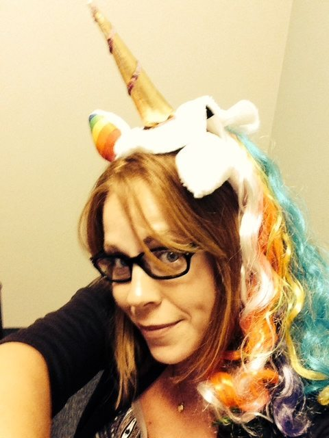 photo of Kym wearing a unicorn headband with a golden horn and rainbow mane