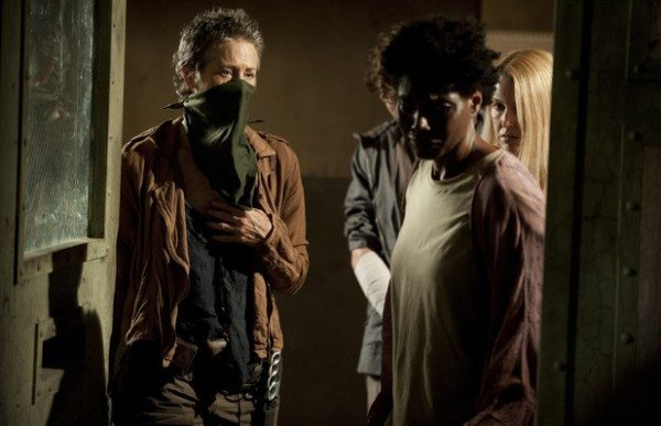"Three people stand around the open door of a room in The Walking Dead 4.03 ""Isolation."""