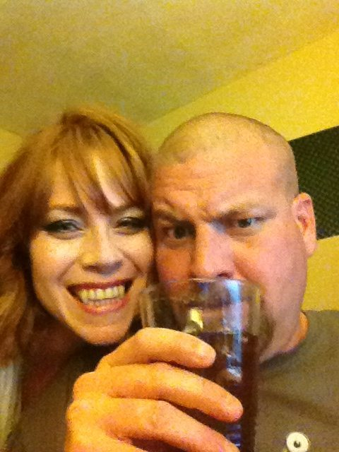 Photo of Kym and husband, Kym is wearing vampire teeth and Jon is holding a glass of soda in front of his face