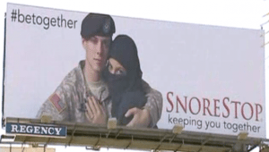 "A billboard with a soldier hugging a person that reads ""SnoreStop."""