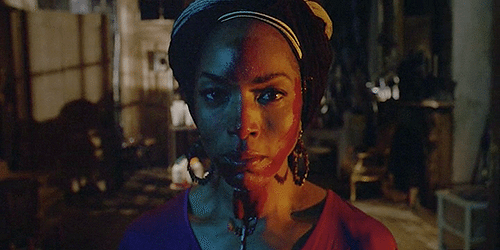"Marie Laveau stares into the camera with blood on her face in American Horror Story episode 3x07, ""Dead."""
