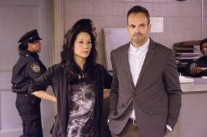 "Sherlock Holmes (Jonny Lee Miller) and Joan Watson (Lucy Liu) stand beside each other in CBS's Elementary 2.06 ""An Unnatural Arrangement"""