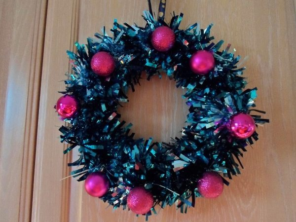 A tinsel wreath with pink baubles hangs on a door.