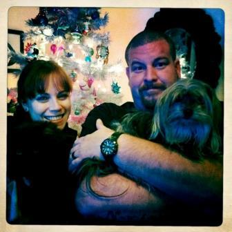 Photo of Kym and Jon holding an adorable Yorkie in front of a silver Christmas tree with pink lights and multi-colored ornaments