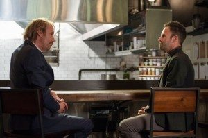 "Mycroft Holmes (Rhys Ifans) and Sherlock Holmes (Jonny Lee Miller) have a conversation in Mycroft's restaurant in CBS's Elementary episode 2.05 ""The Marchioness."""