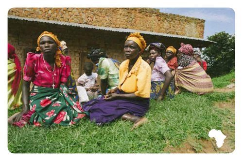 photo of African women sitting on a lawn in front of a building, in the forefront one wears a yellow top and purple skirt, the next wears a pink top with a floral skirt