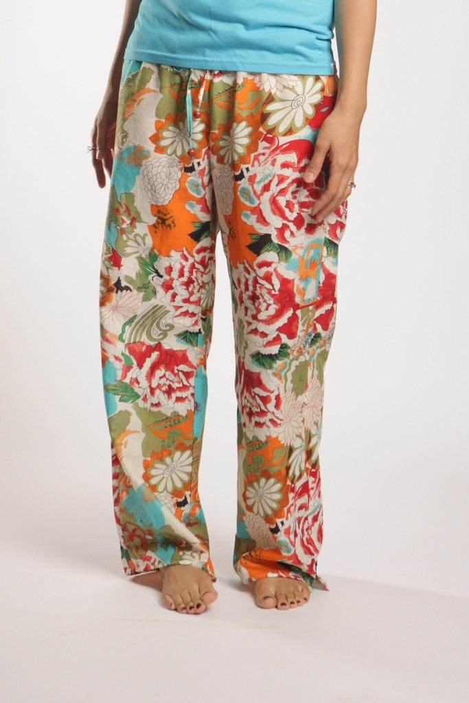 photo of a woman's lower half in a blue tee with brightly colored flower print pajama pants